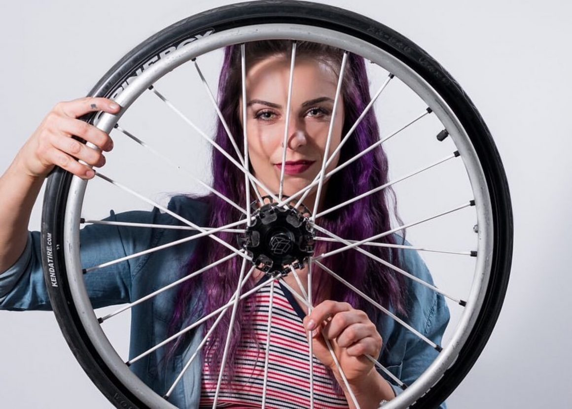 Jesi holding a spinerygy wheelchair wheel with 24 white spokes and a Kenda tire in front of her face.
